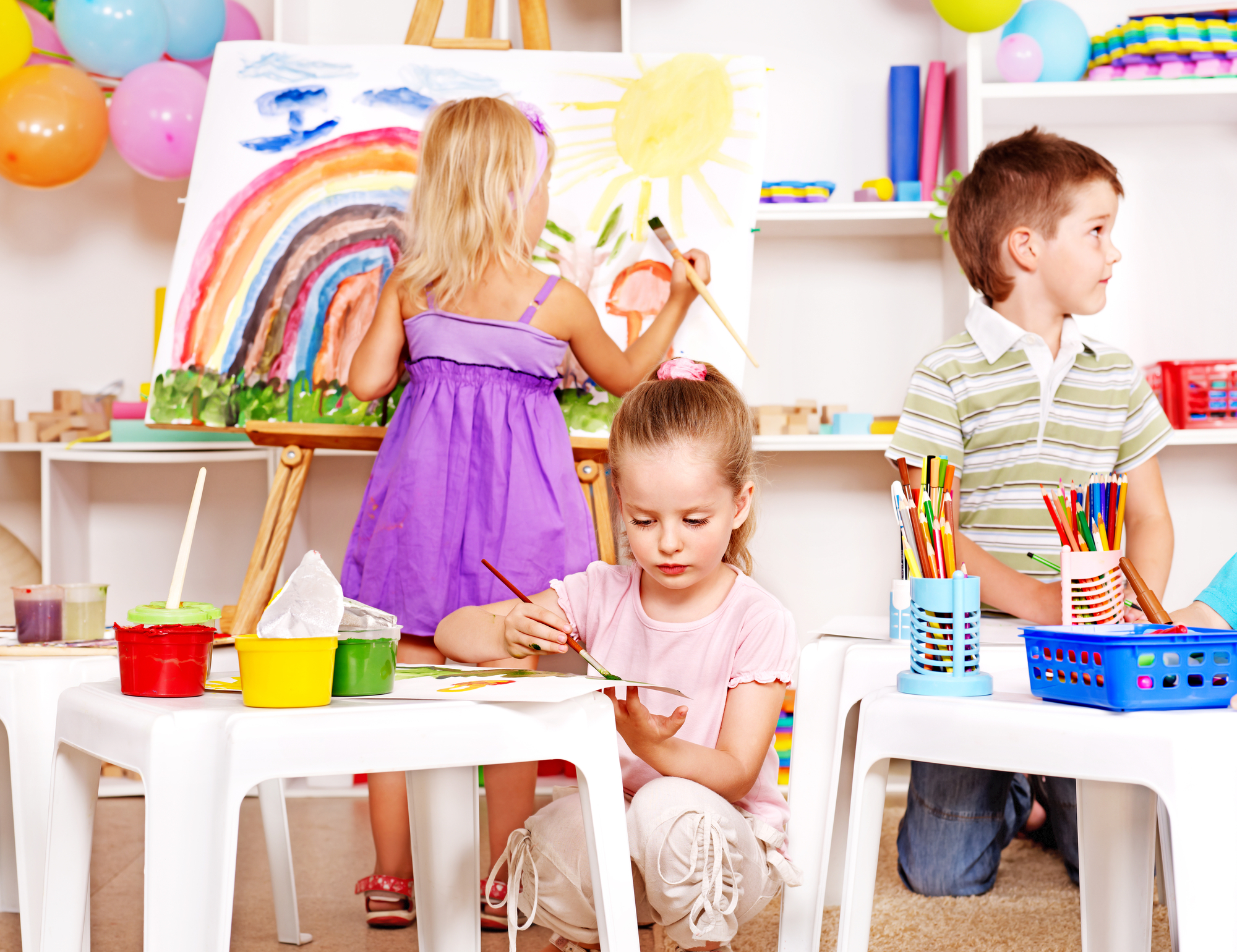 Group children painting at easel in school.